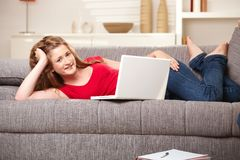 Sourire de l'adolescence avec l'ordinateur portatif sur le sofa à la maison Photo stock