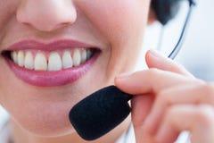 Sourire de la jolie brune utilisant l'écouteur Photographie stock libre de droits