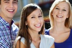 Sourire des trois jeunes Photographie stock libre de droits