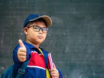 Sourire en verre d'usage de garçon et support heureux devant le blackbo images libres de droits