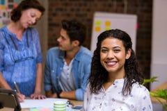 Sourire et collègues de cadre commercial discutant à l'arrière-plan photos stock