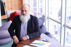 Sourire et entretien de portrait d'homme de directeur d'ancien à l'appareil-photo avec la fin de support Images stock