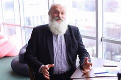 Sourire et entretien de portrait d'homme de directeur d'ancien à l'appareil-photo avec la fin de support Photo stock