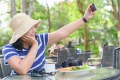Sourire et selfie de femme de voyageur avec le petit déjeuner Photos stock