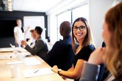 Sourire exécutif femelle à l'appareil-photo pendant la présentation de travail Photo stock