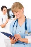 Sourire femelle d'infirmière de jeunes de docteur d'équipe médicale Photo libre de droits