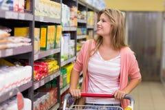 Sourire femme assez blonde regardant l'étagère et achat produits photos stock