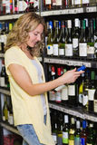 Sourire femme assez blonde regardant la bouteille de vin Images libres de droits