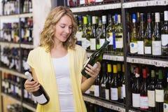 Sourire femme assez blonde regardant la bouteille de vin Photographie stock