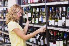 Sourire femme assez blonde regardant la bouteille de vin Photo stock