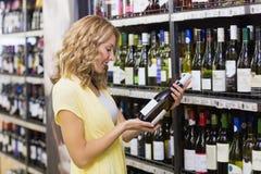 Sourire femme assez blonde regardant une bouteille de vin Photos stock