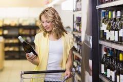Sourire femme assez blonde regardant une bouteille de vin Image libre de droits