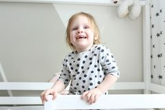 Sourire heureux 2 ans de petite fille dans son lit à la maison Photographie stock libre de droits