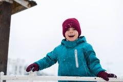 Sourire heureux de chéri jeux de garçon pendant l'hiver dans le terrain de jeu l'enfant utilise un chapeau rouge, une veste bleue images libres de droits