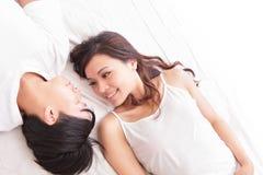Sourire heureux de couples regardant entre eux dans le lit Photo libre de droits