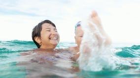 Sourire heureux de fils et de mère, regardant l'appareil-photo faisant l'éclaboussure dans le mouvement lent de mer clips vidéos