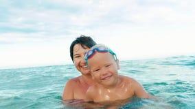 Sourire heureux de fils et de mère, regardant l'appareil-photo faisant l'éclaboussure dans le mouvement lent de mer banque de vidéos