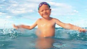 Sourire heureux de garçon, regardant l'appareil-photo faisant l'éclaboussure dans le mouvement lent de mer clips vidéos