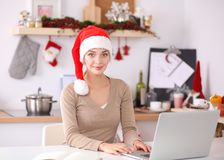 Sourire heureux de jeune femme heureux ayant l'amusement avec des préparations de Noël utilisant le chapeau de Santa Image libre de droits