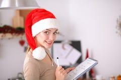 Sourire heureux de jeune femme heureux ayant l'amusement avec des préparations de Noël utilisant le chapeau de Santa Photos stock