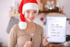 Sourire heureux de jeune femme heureux ayant l'amusement avec des préparations de Noël utilisant le chapeau de Santa Photographie stock libre de droits