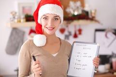 Sourire heureux de jeune femme heureux ayant l'amusement avec des préparations de Noël utilisant le chapeau de Santa Photos libres de droits