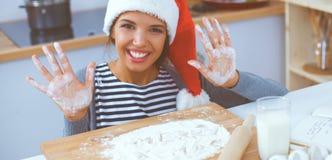 Sourire heureux de jeune femme heureux ayant l'amusement avec des préparations de Noël utilisant le chapeau de Santa photographie stock