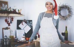 Sourire heureux de jeune femme heureux ayant l'amusement avec des préparations de Noël utilisant le chapeau de Santa images stock