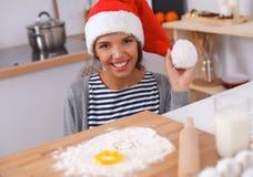 Sourire heureux de jeune femme heureux ayant l'amusement avec des préparations de Noël utilisant le chapeau de Santa Image stock