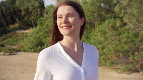 Sourire heureux de portrait de la jeune femme marchant en parc vert Vent soufflant ses cheveux dans le mouvement lent clips vidéos