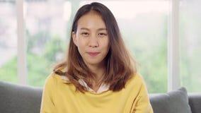 Sourire heureux de sentiment asiatique de femme d'adolescent et regard au moment de caméra pour détendre dans son salon à la mais banque de vidéos