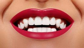 Sourire heureux en gros plan avec les dents blanches saines, maquillage rouge lumineux de lèvres Soin de cosmétologie, d'art dent photo stock