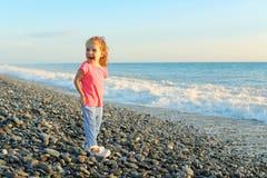 Sourire heureux mignon peu de fille sur le bord de la mer images stock