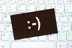Sourire heureux sur la carte de papier, concept de protection de l'ordinateur Photos stock