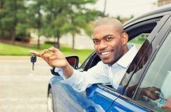 Sourire, jeune homme s'asseyant dans sa nouvelle voiture montrant des clés Photos stock