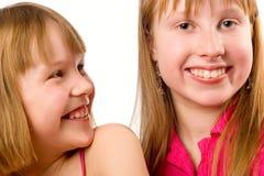Sourire joyeux de deux filles au-dessus du blanc Photographie stock libre de droits