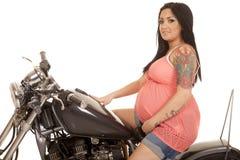 Sourire latéral enceinte de chemise de rose de tatouage de femme Photographie stock libre de droits