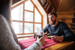 Sourire mangeur d'hommes et parler à l'amie en cottage en bois Images stock