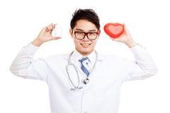Sourire masculin asiatique de docteur avec la bouteille rouge de coeur et de pilule Photos stock