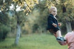 Sourire mignon d'enfant en bas âge dans le costume, chemises, espadrilles sous l'arbre, mode Images libres de droits