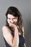 Sourire mignon de jeune femme, touchant son visage pour l'embarras photo stock