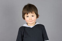 Sourire mignon de petit garçon au-dessus de gris Photos stock
