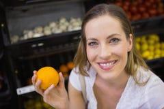 Sourire oranges de achat de femme assez blonde Images stock