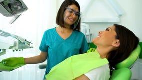 Sourire patient de dame heureuse au dentiste après la procédure, contrôle régulier dans la clinique photographie stock libre de droits