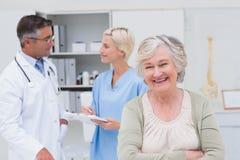 Sourire patient tandis que médecin et infirmière discutant à l'arrière-plan Image libre de droits