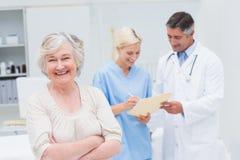 Sourire patient tandis que médecin et infirmière discutant dans la clinique Photographie stock