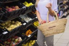 Sourire pommes de achat de femme assez blonde Photographie stock libre de droits