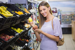 Sourire pommes de achat de femme assez blonde Image stock