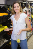 Sourire pommes de achat de femme assez blonde Photos stock