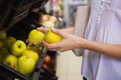 Sourire pommes de achat de femme assez blonde Photo stock